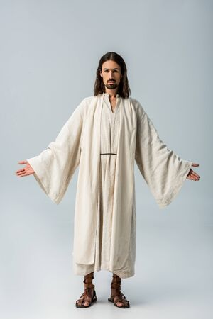 religious man in jesus robe standing with outstretched hands on grey