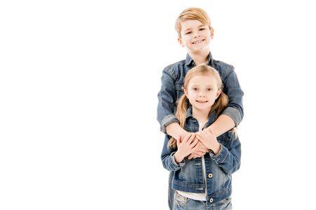 bambini felici che abbracciano e guardano la telecamera isolata su bianco