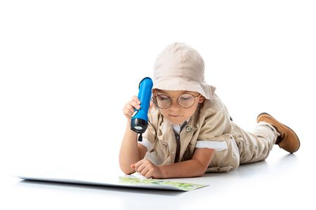 focused explorer child in hat and glasses holding flashlight and looking at map on white