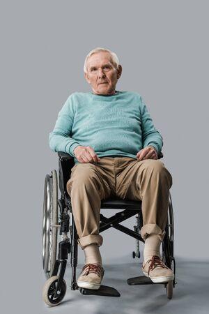 sad senior man sitting in wheelchair and looking at camera on grey Stockfoto