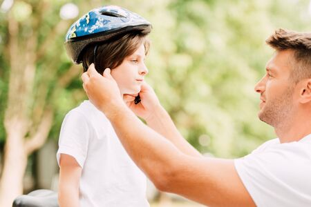 side view of father putting helmet on son while boy looking at dad