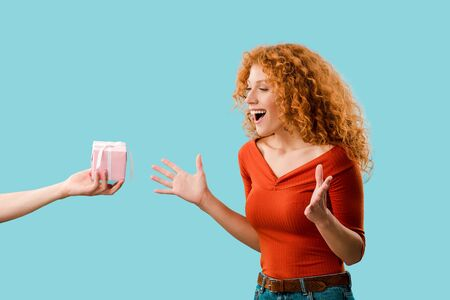 excited redhead girl with gift box isolated on blue