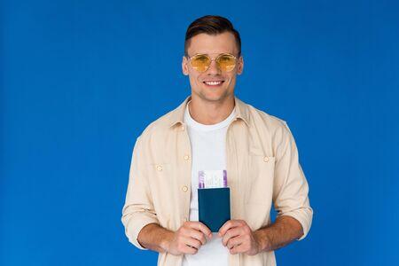 widok z przodu uśmiechniętego podróżnika w okularach przeciwsłonecznych trzymającego paszport z biletem lotniczym na niebieskim tle Zdjęcie Seryjne