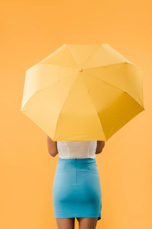 back view of woman standing with umbrella isolated on yellow