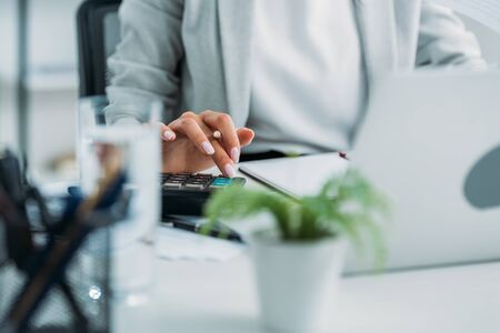 Ausgeschnittene Ansicht einer Frau in formeller Kleidung mit Taschenrechner