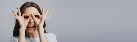 panoramic shot of beautiful happy girl showing tongue and ok signs isolated on grey