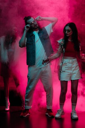 man and girl dancing in nightclub with neon pink smoke