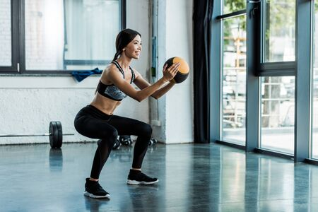 cheerful sportswoman holding ball and doing squat exercise