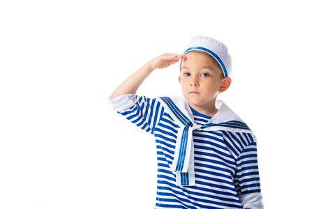 poważne dziecko w wieku przedszkolnym w kostiumie marynarza, salutujące i patrzące na kamerę na białym tle