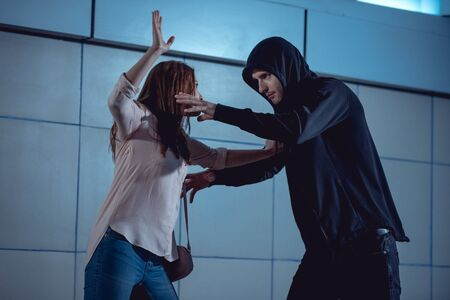 woman defending herself from attacking thief in underpass