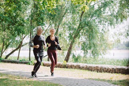 sportive mature sportsman and sportswoman running together in park Foto de archivo - 130116534
