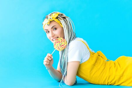 smiling girl with dreadlocks lying and licking lollipop on turquoise