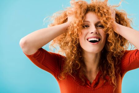 portrait of excited redhead girl isolated on blue
