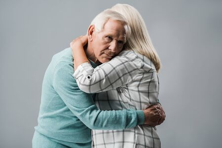 sad retired man hugging senior wife and looking at camera isolated on grey