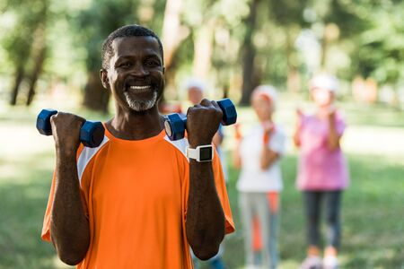 selective focus of happy african american man standing with dumbbells near pensioners