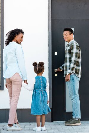 full length view of african american father opening door while mother and kid walking to man Standard-Bild