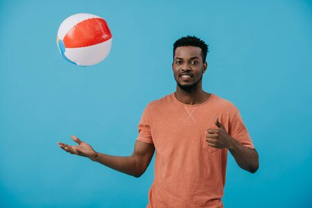 cheerful african american man throwing beach ball in air isolated on blue 写真素材