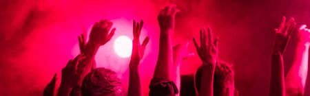 panoramic shot of back view of people with raised hands during rave party in nightclub