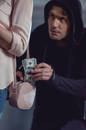 thief stealing dollar banknotes from bag of woman Stockfoto