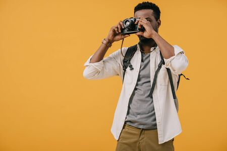 african american photographer covering face with digital camera isolated on orange