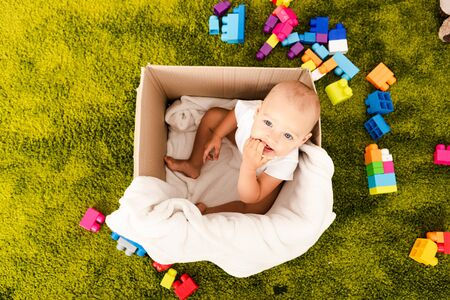 Top view of cute little child sitting in cardboard box with white blanket on green floor