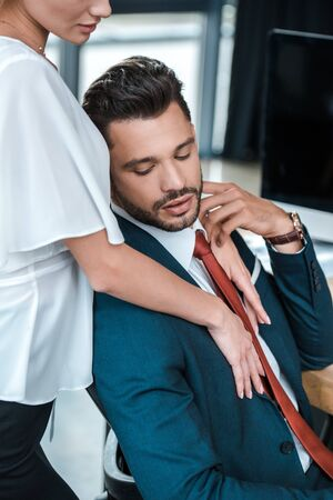 cropped view of woman standing near handsome bearded man in office