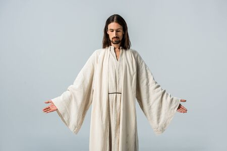 mężczyzna w szacie Jezusa stojący z wyciągniętymi rękami na szarym tle Zdjęcie Seryjne