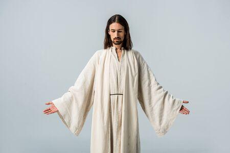 Mann in Jesus-Gewand, der mit ausgestreckten Händen isoliert auf Grau steht Standard-Bild