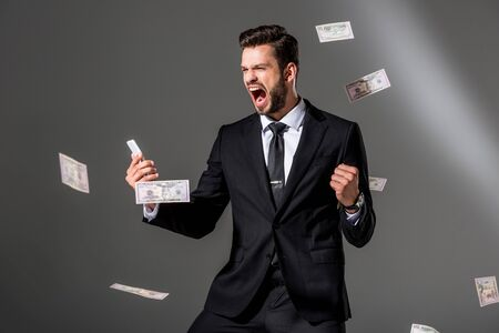 excited businessman with smartphone near falling dollar banknoteson on grey