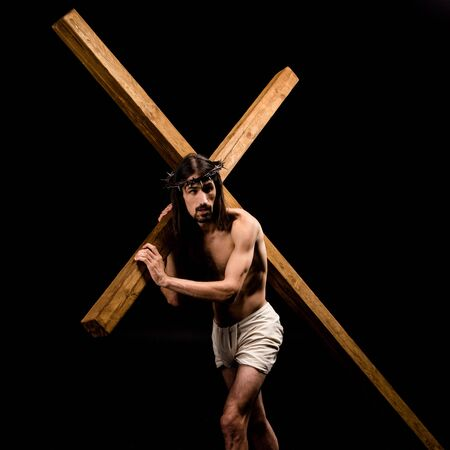 jesus in wreath holding wooden cross and standing isolated on black Stock Photo