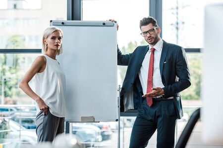 handsome businessman gesturing near attractive woman standing in office