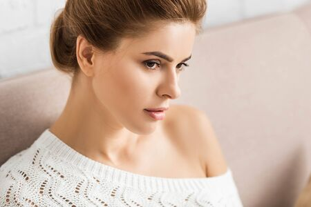 attractive woman in white sweater looking away in apartment