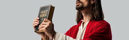 panoramic shot of jesus holding holy bible isolated on grey