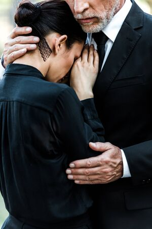 cropped view of upset senior man hugging woman on funeral