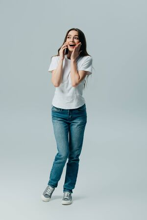 excited surprised beautiful girl in white t-shirt and jeans talking on smartphone isolated on grey Stockfoto