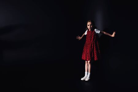 frightened, lonely child looking at camera while standing on black background Stockfoto