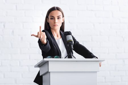 irritated lecturer standing at podium tribune while showing middle finger at camera