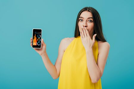 shocked beautiful girl in yellow dress showing smartphone with financial app isolated on turquoise Stock Photo
