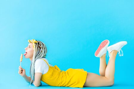 girl with dreadlocks lying and licking lollipop on turquoise