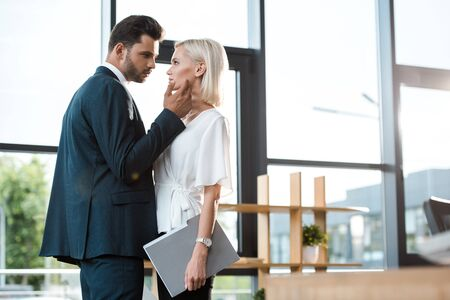 handsome businessman touching face of attractive girl while flirting in office