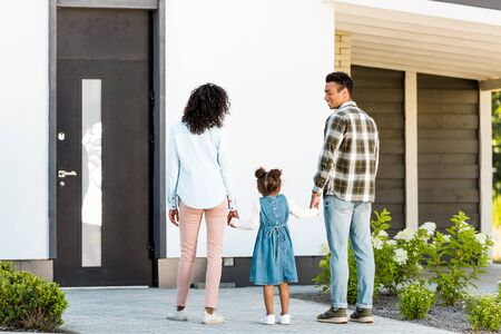 full length view of african american family standing near new house while parents holding hands with kid Stockfoto