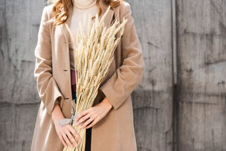 cropped view of woman in coat holding spikes outside