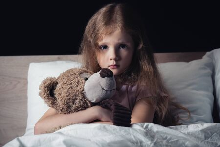scared kid embracing teddy bear while sitting under blanket and looking at camera isolated on black