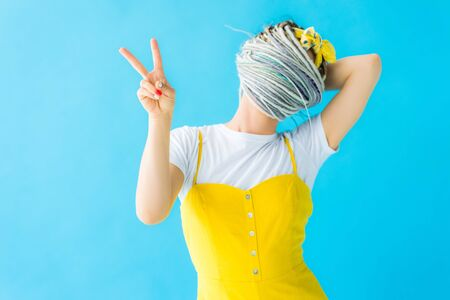 girl with dreadlocks covering face with hair and showing peace sign isolated on turquoise