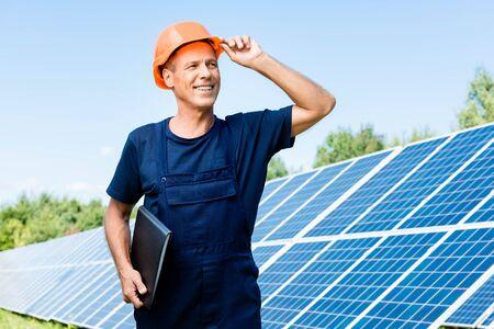 bel ingegnere in maglietta e elmetto arancione che sorride e tiene in mano una cartella