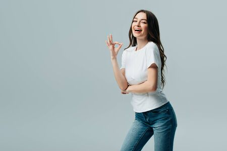 beautiful girl in white t-shirt showing ok sign isolated on grey