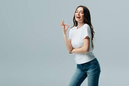 hermosa chica en camiseta blanca mostrando signo ok aislado en gris
