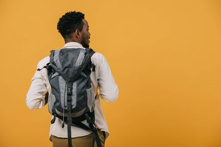 african american man standing with backpack isolated on orange