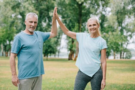 cheerful sportsman and sportswoman giving high five while smiling at camera