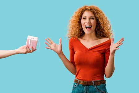 excited redhead woman with gift box isolated on blue